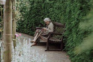 Starsza kobieta siedząca na ławce